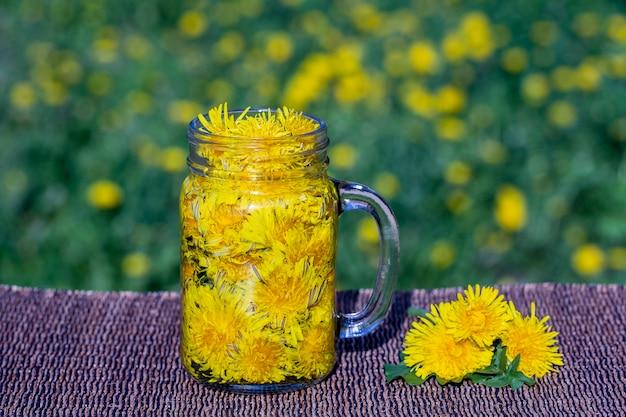 Napój herbaty z żółtym kwiatem mniszka lekarskiego w szklanym kubku na stole, na zewnątrz