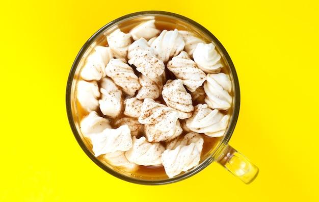 Napój kakaowy z piankami i proszkiem czekoladowym w szklanym kubku na żółtym tle widok z góry