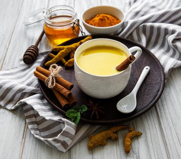 Napój latte z żółtą kurkumą. złote mleko z cynamonem, kurkumą, imbirem i miodem na białej drewnianej powierzchni.