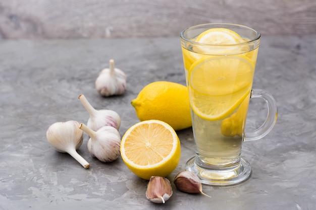 Napój leczniczy z cytryną i czosnkiem w szklance na stole. medycyna alternatywna, leczenie środkami ludowymi.