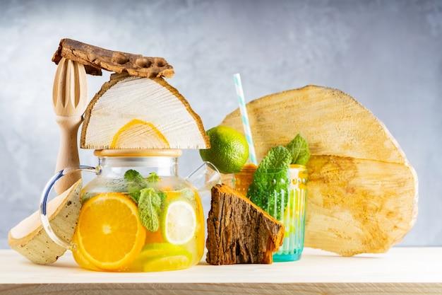 Napój lemoniadowy z wody, cytryny, pomarańczy i liści mięty w przezroczystym czajniczku. mrożona herbata limonkowo-miętowa i kawałki drewna. kreatywna kompozycja
