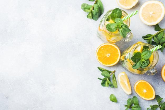 Napój lemoniady wody sodowej, cytryny i liści mięty w słoiku na jasnym tle.