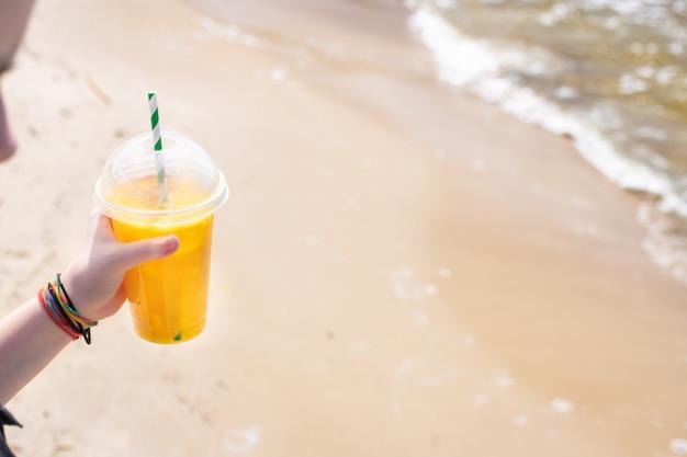 Napój lodowy sok żółty lemoniada na plaży brzeg morza pomarańczowy świeży orzeźwiający napój relaks