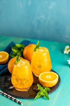 Napój pomarańczowy z lodem. dwie szklanki napoju pomarańczowego z świeżą miętą