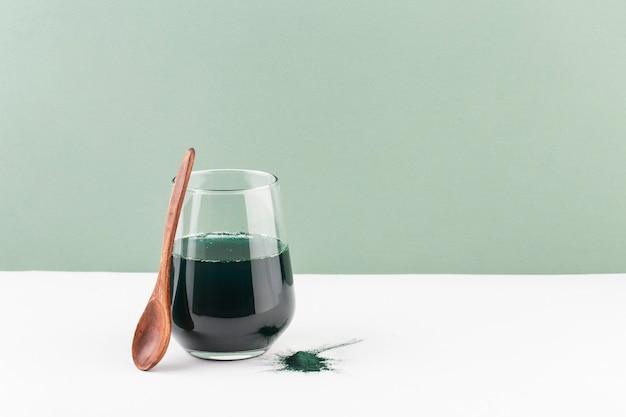 Napój spirulina w szklance na białym stole, zielona przestrzeń, minimalizm