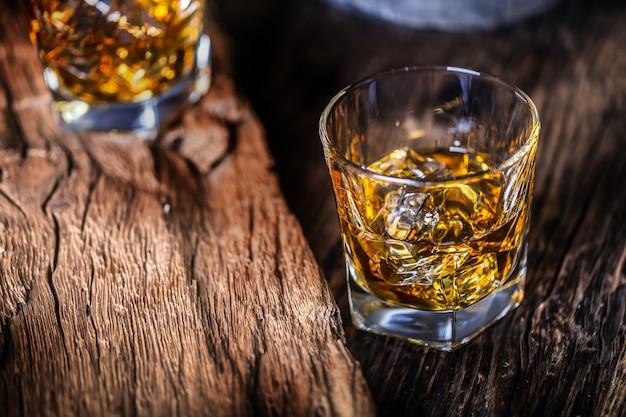 Napój whisky. napoje whisky na rustykalnym drewnie dębowym z kostkami lodu.
