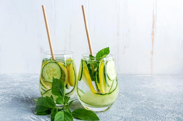 Napój wodny detox z ogórkiem i cytryną na jasnoszarym stole i białej ścianie w tle