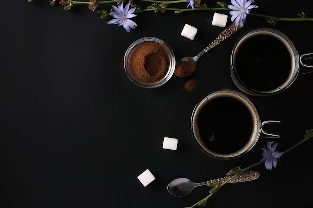 Napój z cykorii w dwóch szklanych filiżankach, z koncentratem i kwiatami na czarnej powierzchni