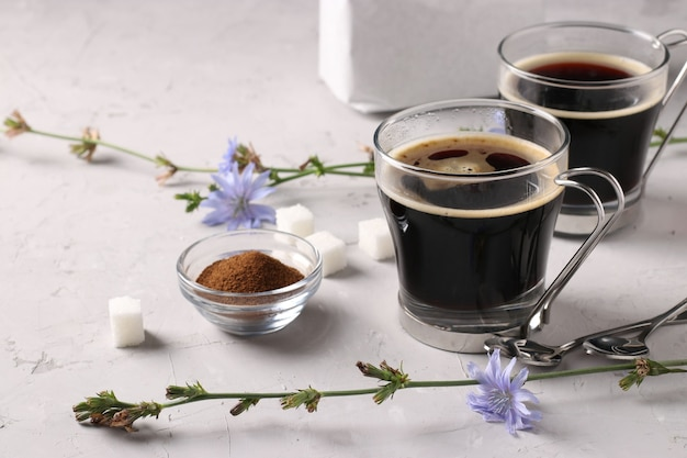 Napój z cykorii w dwóch szklanych filiżankach, z koncentratem i kwiatami na szarym tle. zdrowy napój ziołowy
