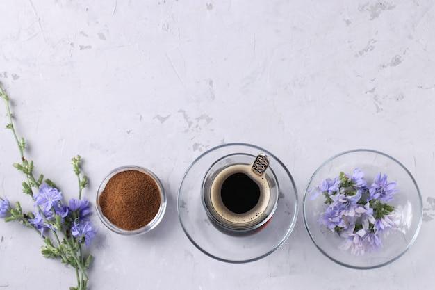 Napój z cykorii w szklanym kubku, z koncentratem i kwiatami na szarej powierzchni