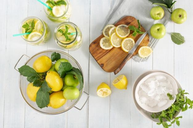 Napój z owoców cytrusowych. świeża lemoniada z jabłkami i cytryną na drewnianym stołowym odgórnym widoku