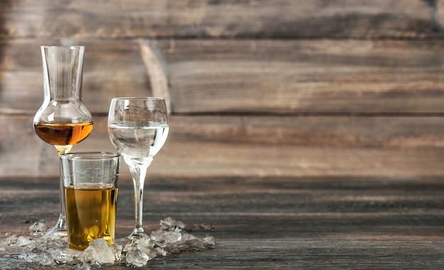 Napoje alkoholowe z lodem na drewnianym tle. whisky, likier, wódka