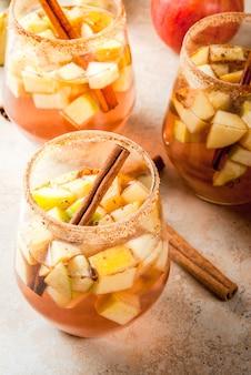 Napoje jesienne i zimowe. ciepła sangria jabłkowa, jabłecznik z kawałkami owoców, cynamon, przyprawy, cukier. w okularach, na kamiennym beżowym stole. ze składnikami. copyspace