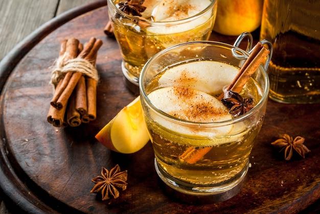Napoje jesienne i zimowe. tradycyjny domowy jabłecznik, koktajl jabłkowy z aromatycznymi przyprawami - cynamonem i anyżem. na starym drewnianym rustykalnym stole, na tacy. copyspace