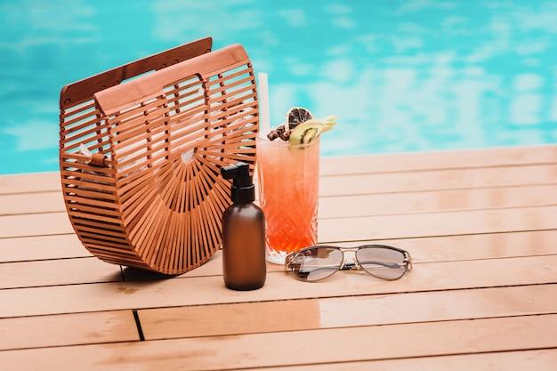 Napoje przy basenie w tropikalnym kurorcie, okulary przeciwsłoneczne i drewniana torba