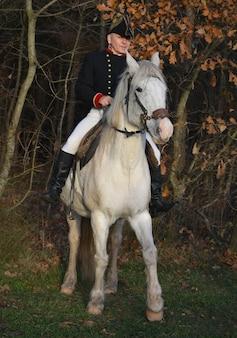 Napoleon bonaparte na białym koniu na tle przyrody.