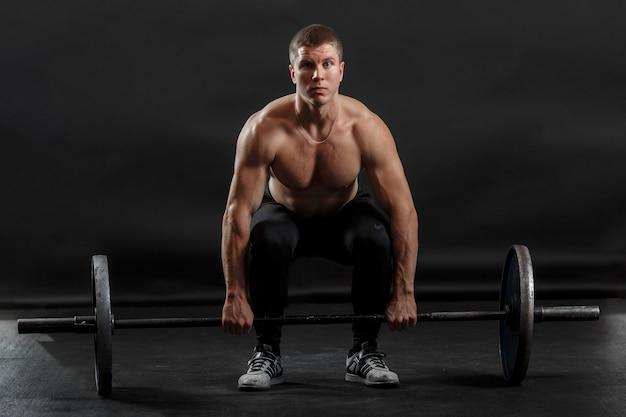 Napompowany mężczyzna robi ćwiczenia sportowe podnosząc sztangę gimnastyczną