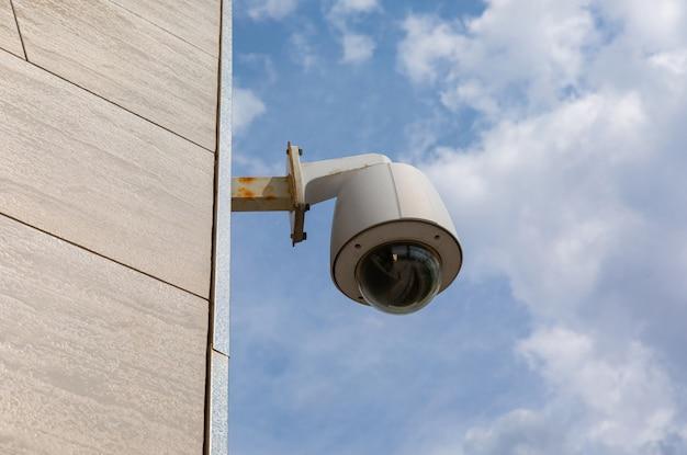 Napowietrzna kamera bezpieczeństwa na fasadzie budynku publicznego lub centrum biurowego.