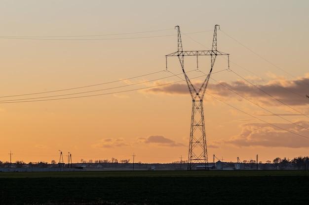 Napowietrzna linia energetyczna na wsi o zachodzie słońca