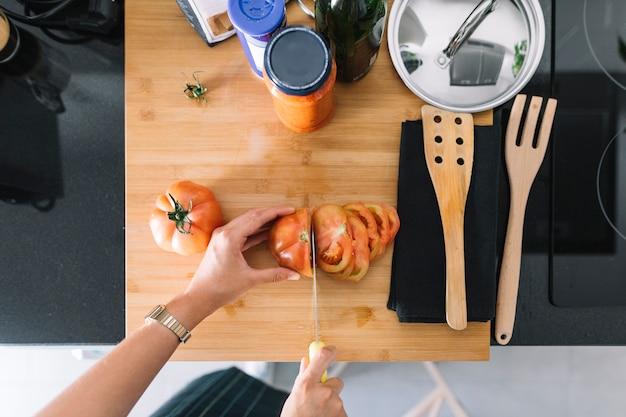 Napowietrznych widok osoby cięcia pomidorów plasterki na blacie kuchennym