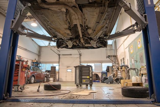 Napraw i sprawdź samochód w warsztacie. doświadczony technik naprawia wadliwą część samochodu. zmieniam opony