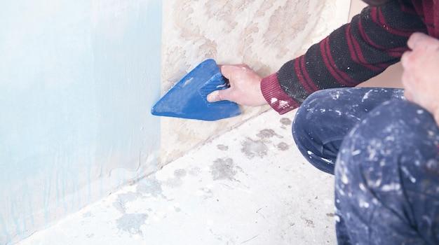 Napraw mieszkanie. pracownik przykleja tapetę do ściany.
