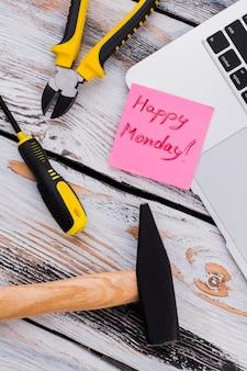 Napraw narzędzia robocze i zanotuj z szczęśliwym poniedziałkowym życzeniem. widok z góry na płasko.