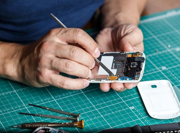 Naprawa elektroniki. technik demontujący smartfon do wglądu.