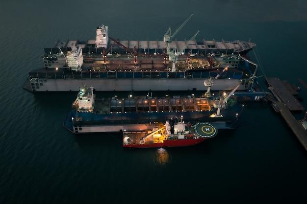 Naprawa i konserwacja zbiorników oleju w stoczni na morzu przemysł w nocy widok z góry z lotu ptaka