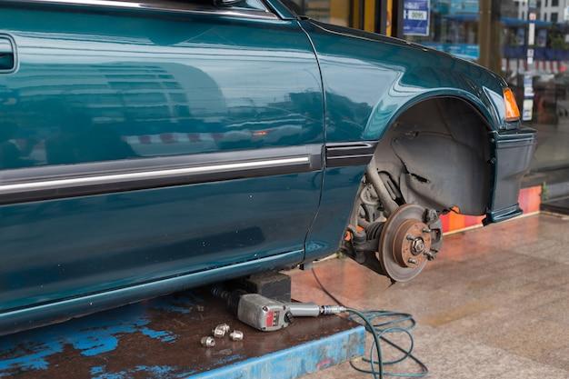 Naprawa koła samochodu na podnośniku w garażu