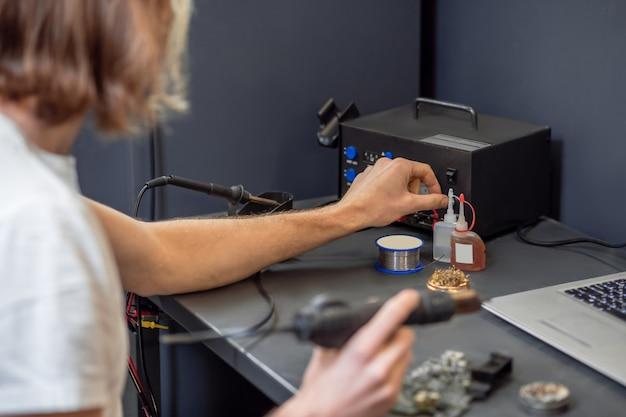 Naprawa, mikroukład. silne męskie dłonie lutujące, wykonując mikroukład w warsztacie za pomocą urządzeń, bez twarzy