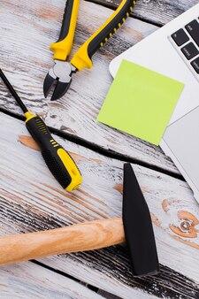 Naprawa narzędzi roboczych i pusta naklejka na miejsce. biały drewniany stół na tle. widok z góry na płasko.