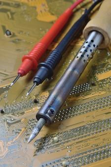 Naprawa płyty głównej komputera. lutownica i szczypce nad mikroukładem ..