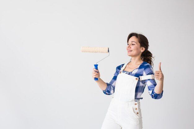 Naprawa, renowacja, koncepcja nowego domu i ludzi - młoda kobieta robi remont i pokaż nam kciuki
