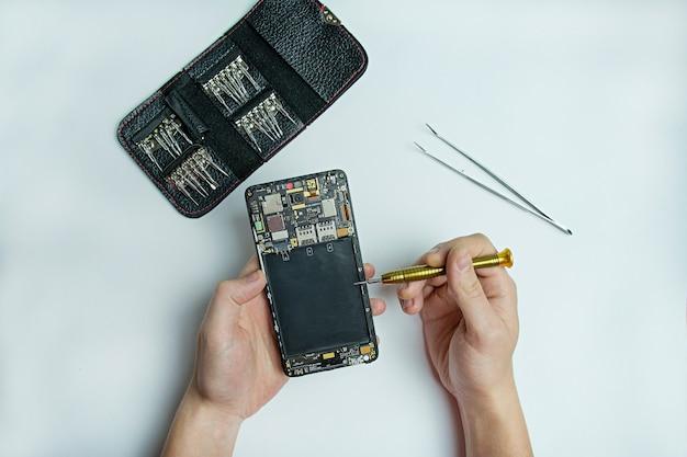 Naprawa smartfona. zdemontowany smartfon w męskich rękach. zestaw naprawczy do smartfona. leżał płasko, widok z góry. miejsce na tekst.