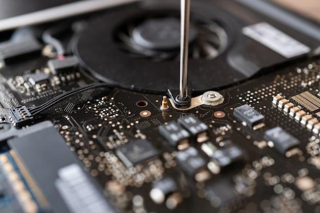 Naprawa uszkodzonej płyty głównej laptopa, technik za pomocą śrubokręta.