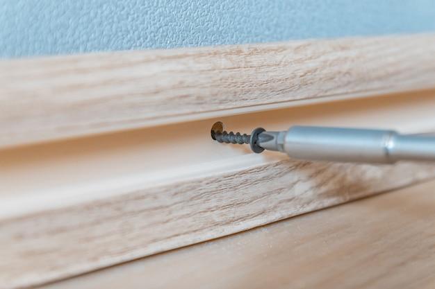 Naprawa w domu. śrubokręt dociska śrubę do lekkiej plastikowej listwy przypodłogowej i ściany