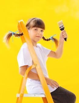 Naprawa w mieszkaniu. smutna dziewczynka maluje ścianę pomarańczową farbą