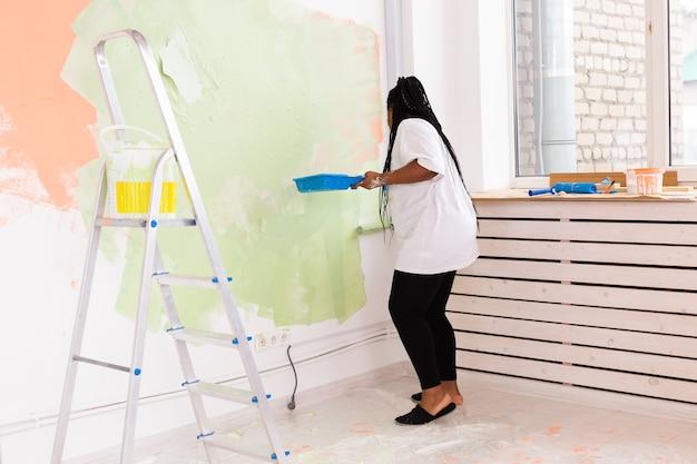 Naprawa w mieszkaniu. szczęśliwa młoda kobieta maluje ścianę farbą.