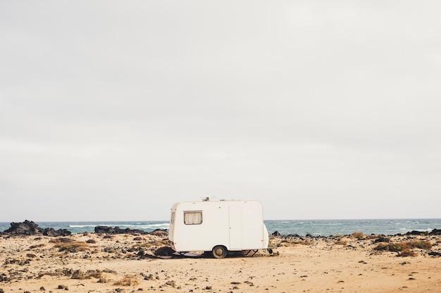 Naprawdę alternatywny styl życia w kontakcie z naturą i samym sobą mieszkając w szczerym polu z małą przyczepą kempingową zaparkowaną na wybrzeżu z widokiem na fale oceanu. niezależność i dzikie l