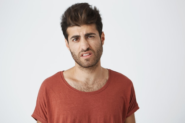 Naprawdę oburzony stylowy chłopak z modną fryzurą ubrany w codzienne ubrania stojący przy białej ścianie, wyrażający nieporozumienie, niechęć lub lekceważenie, czujący niechęć do czegoś
