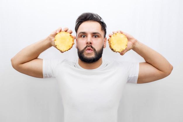 Naprawdę zdumiony młody człowiek stoi i patrzy. zakrywa uszy dwiema połówkami jednego ananasa. facet się boi. rozproszony człowiek.