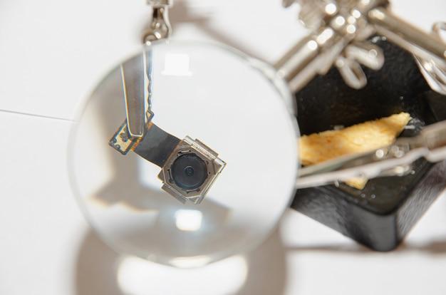 Naprawia telefon i bada drobne szczegóły za pomocą lupy