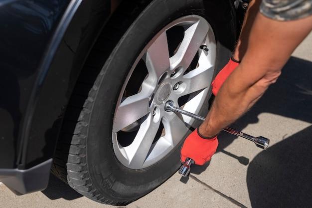 Naprawianie i sprawdzanie opony koła samochodu z ręcznym zbliżeniem narzędzia metalowego