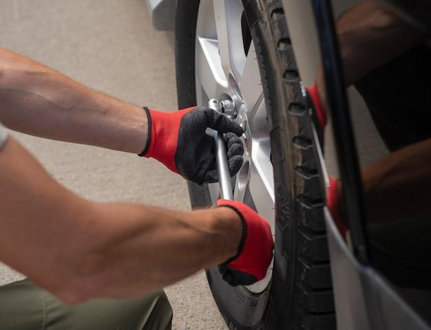 Naprawianie i sprawdzanie opony koła samochodu za pomocą ręcznego narzędzia metalowego z bliska