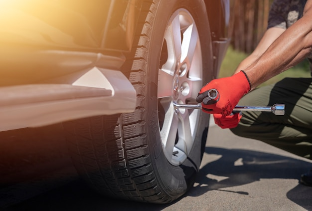 Naprawianie inspekcji i sprawdzanie opony koła samochodu za pomocą narzędzia ręcznego