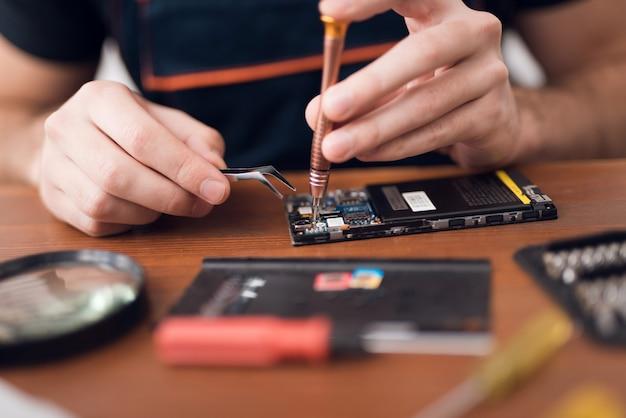 Naprawianie naprawy telefonu komórkowego w serwisie gwarancyjnym.