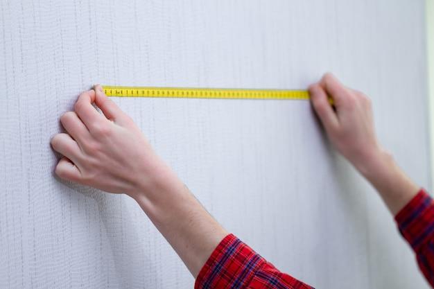 Naprawy domowe i pomiar długości ściany za pomocą taśmy mierniczej
