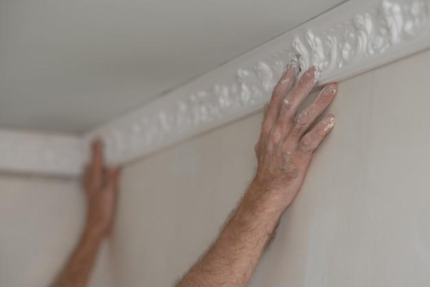 Naprawy domowe. zbliżenie dłoni pracownika mocowania bagietki do sufitu.