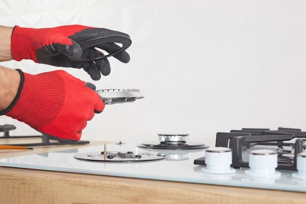 Naprawy i mocowanie panelu sterowania gazem. ręka mężczyzny w rękawicach ochronnych naprawia płytę grzejną płyty grzejnej.